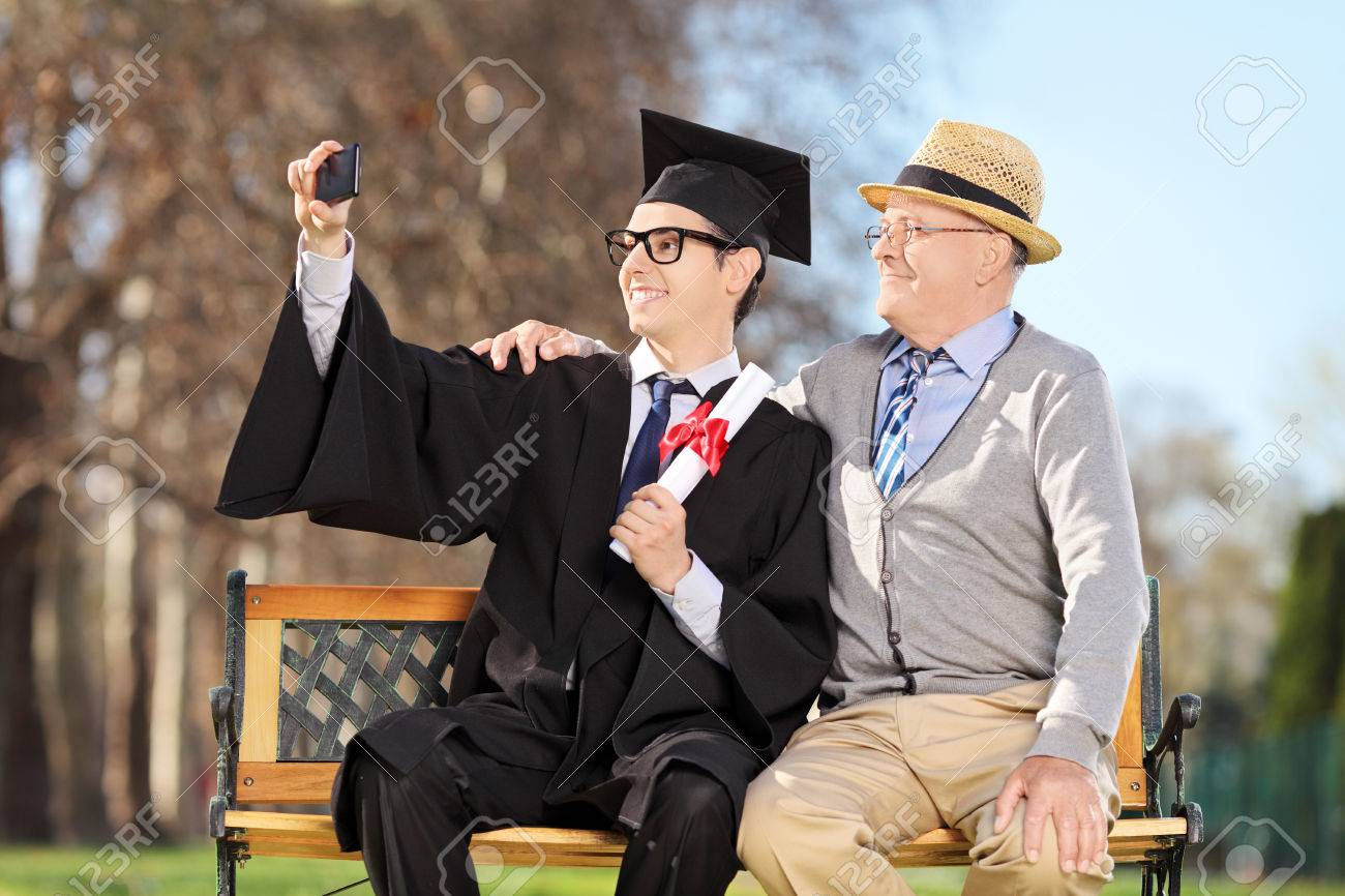 Male graduate and his father taking selfie outdoors Stock Photo - 27315794