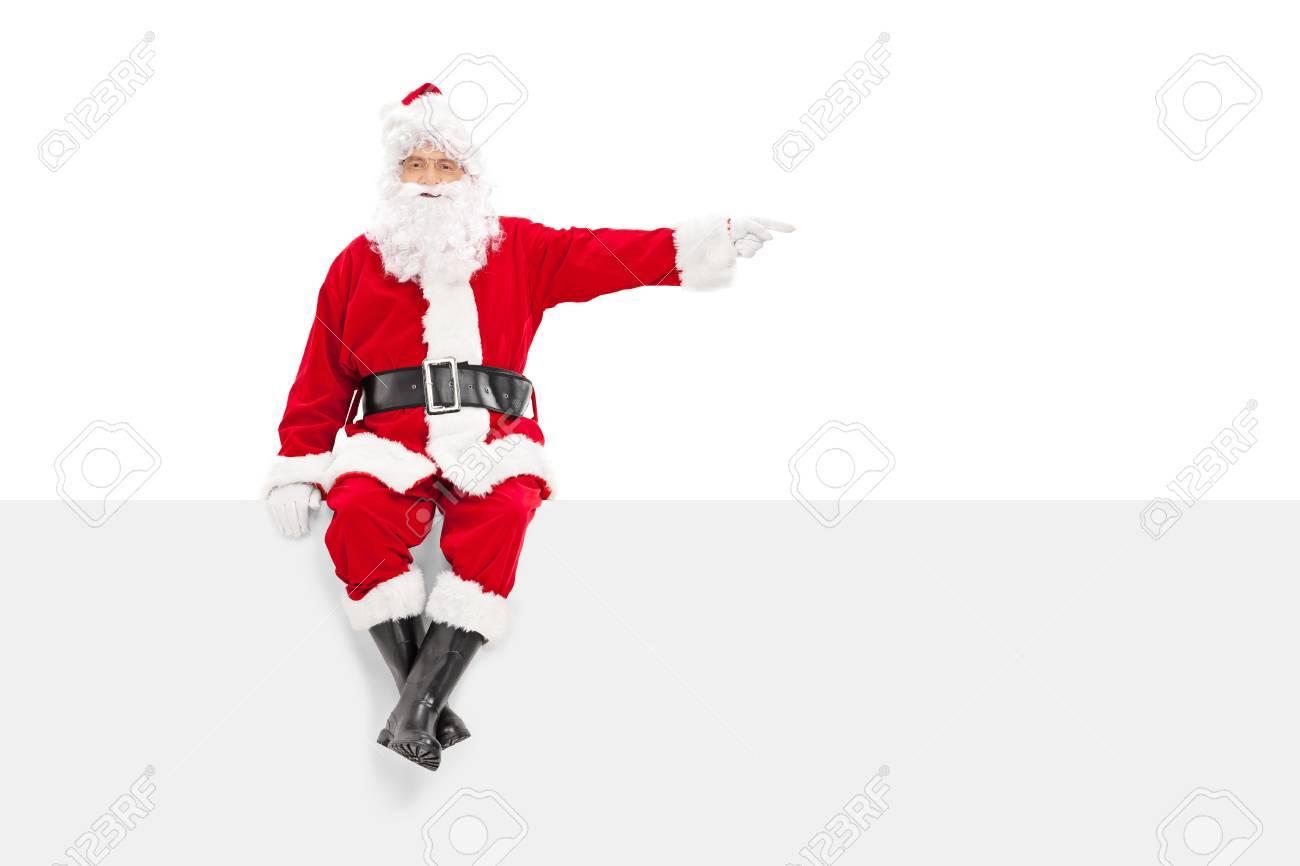 Pere Noel Assis Père Noël Assis Sur Un Panneau Et Pointant Avec Le Doigt Isolé Sur