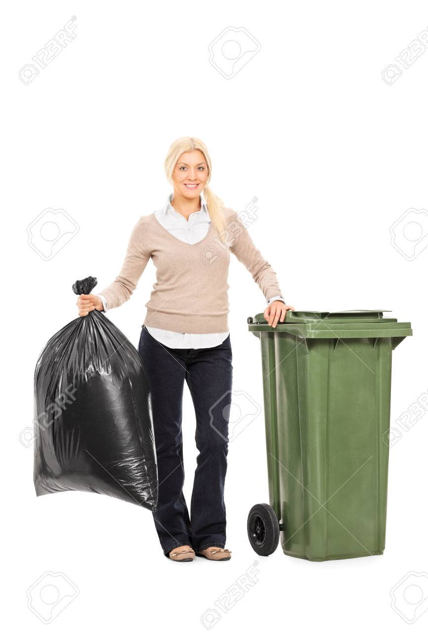 Full length portrait of a woman holding a trash bag next to a garbage bin isolated on white background - 34007973