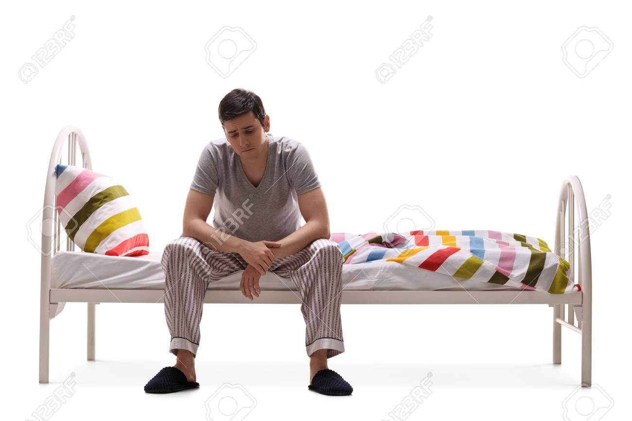5b76589e56 Sad man in pajamas sitting on a bed isolated on white background Stock  Photo - 37120817