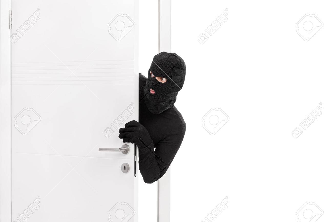 studio shot of a stealthy thief breaking into a room through stock