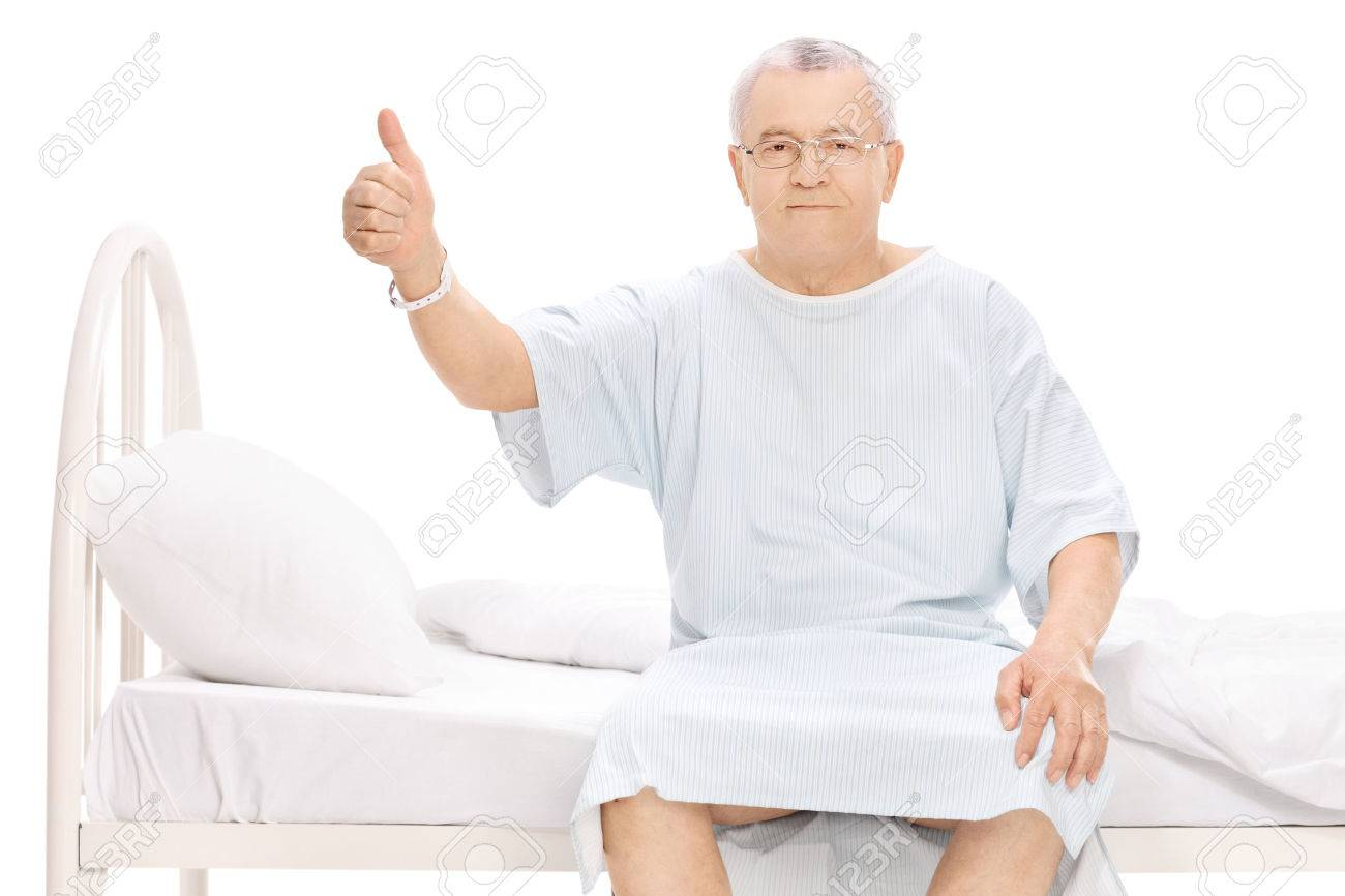 mature patient sitting on a hospital bed, giving a thumb up and