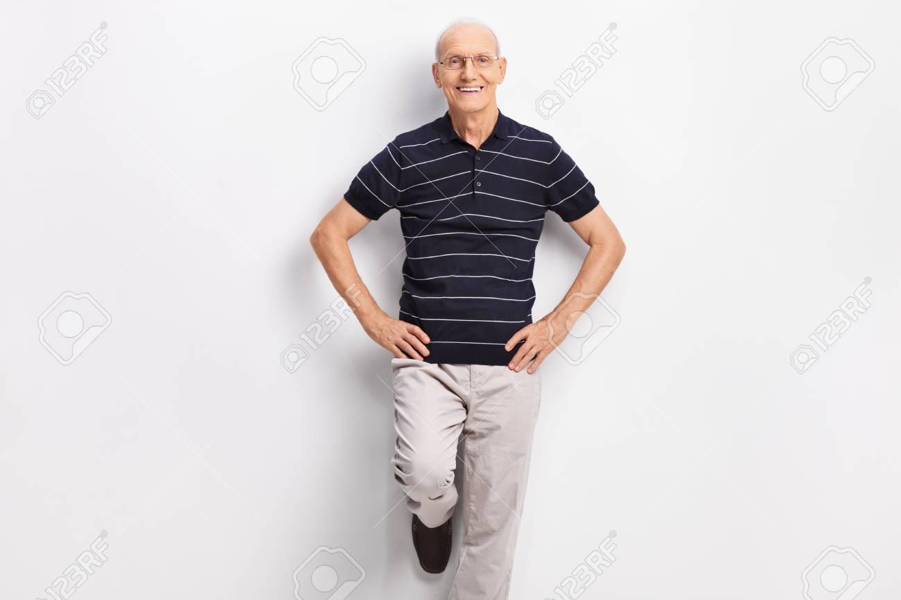 cad868319 Caballero senior alegre en ropa casual apoyado contra una pared y mirando a  la cámara