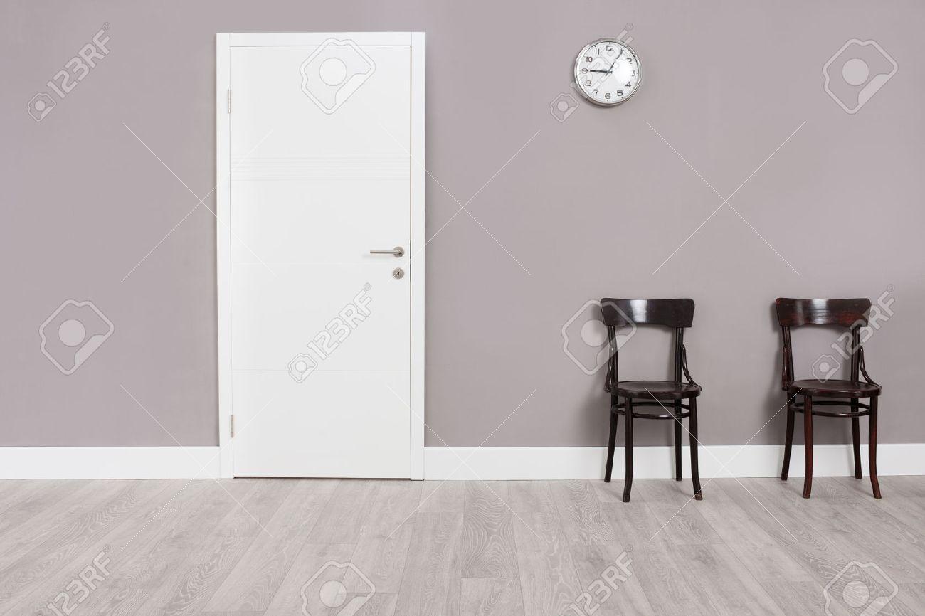 Zwei Hölzerne Stühle In Einem Warteraum Mit Einer Uhr über Ihnen An ...