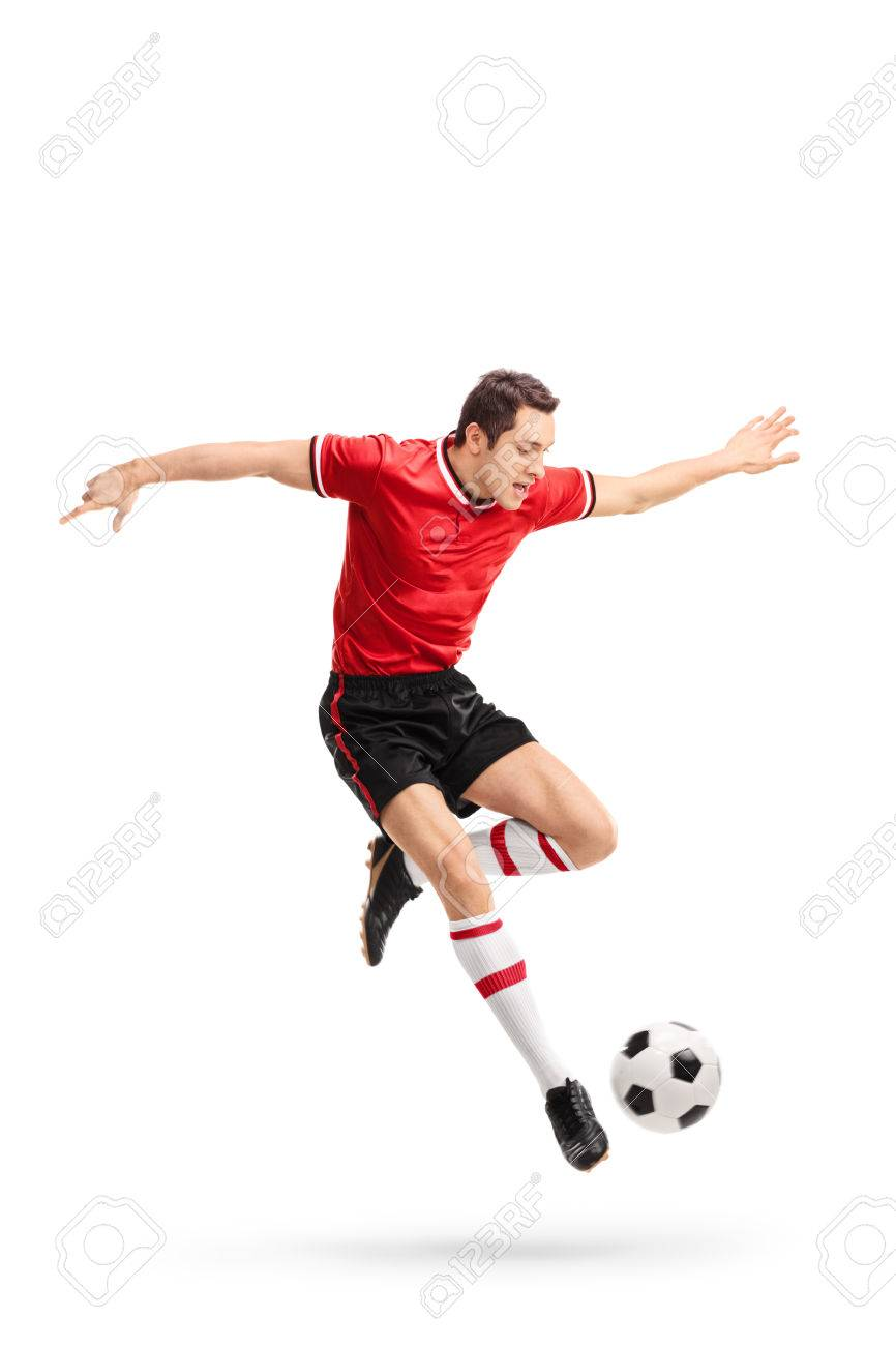 af15ba8f3 Full length portrait of a young football player in red jersey kicking a ball  in mid