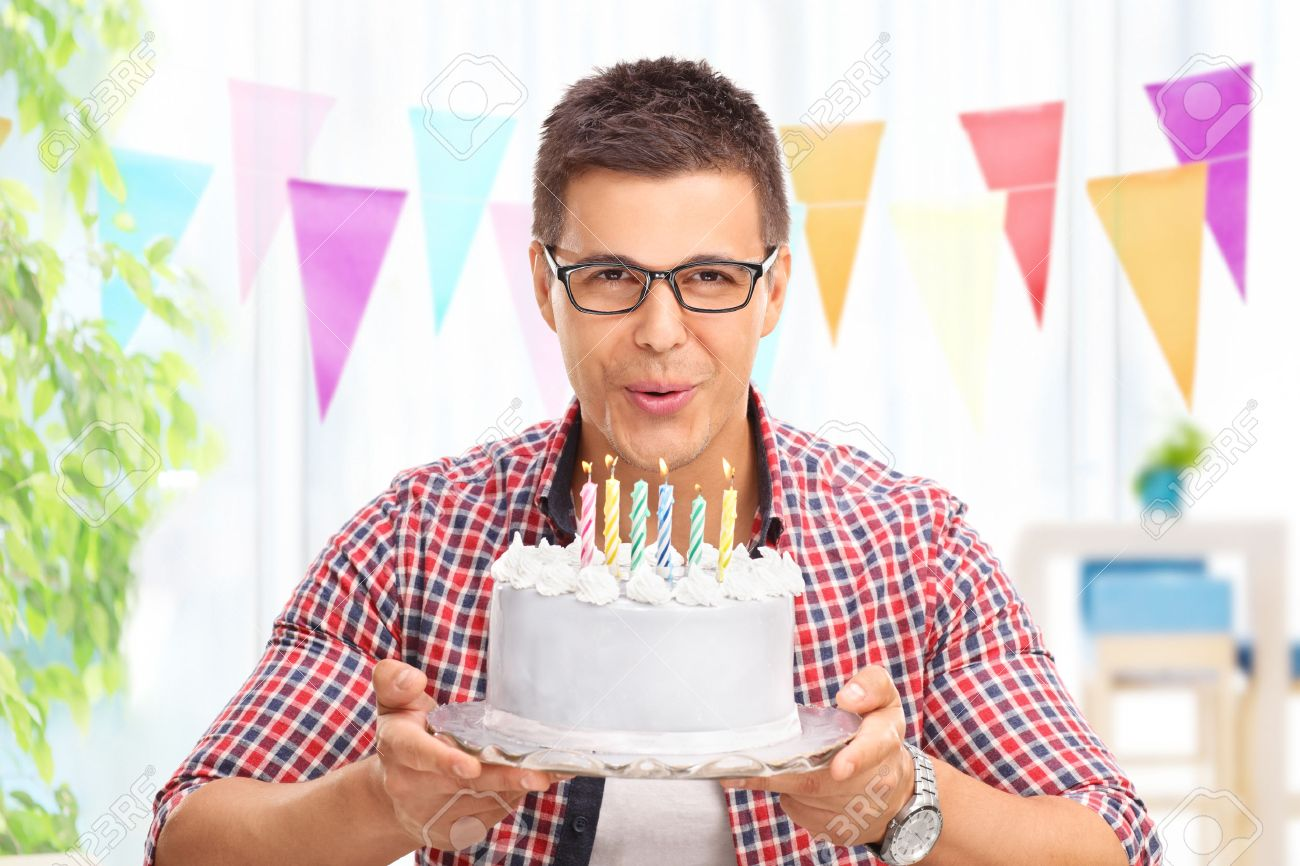 Joyful Young Man Blowing Candles On A Birthday Cake And Looking