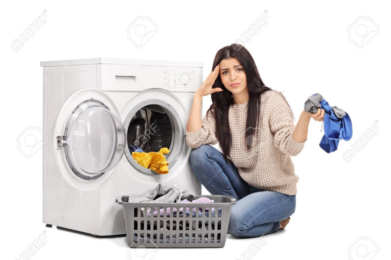 Studio shot of a sad woman emptying a washing machine and looking at the camera isolated on white background - 50659132