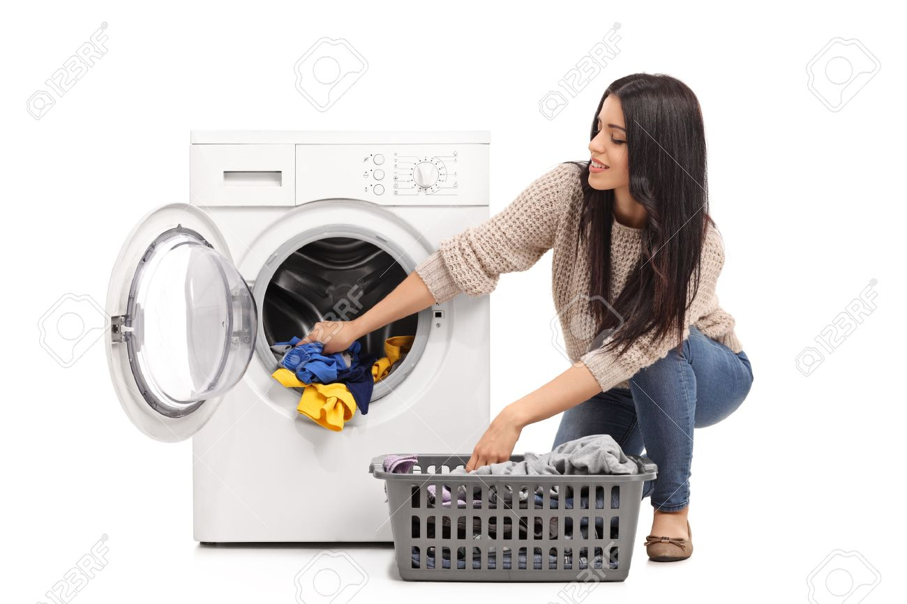 Young woman emptying a washing machine isolated on white background - 51993721