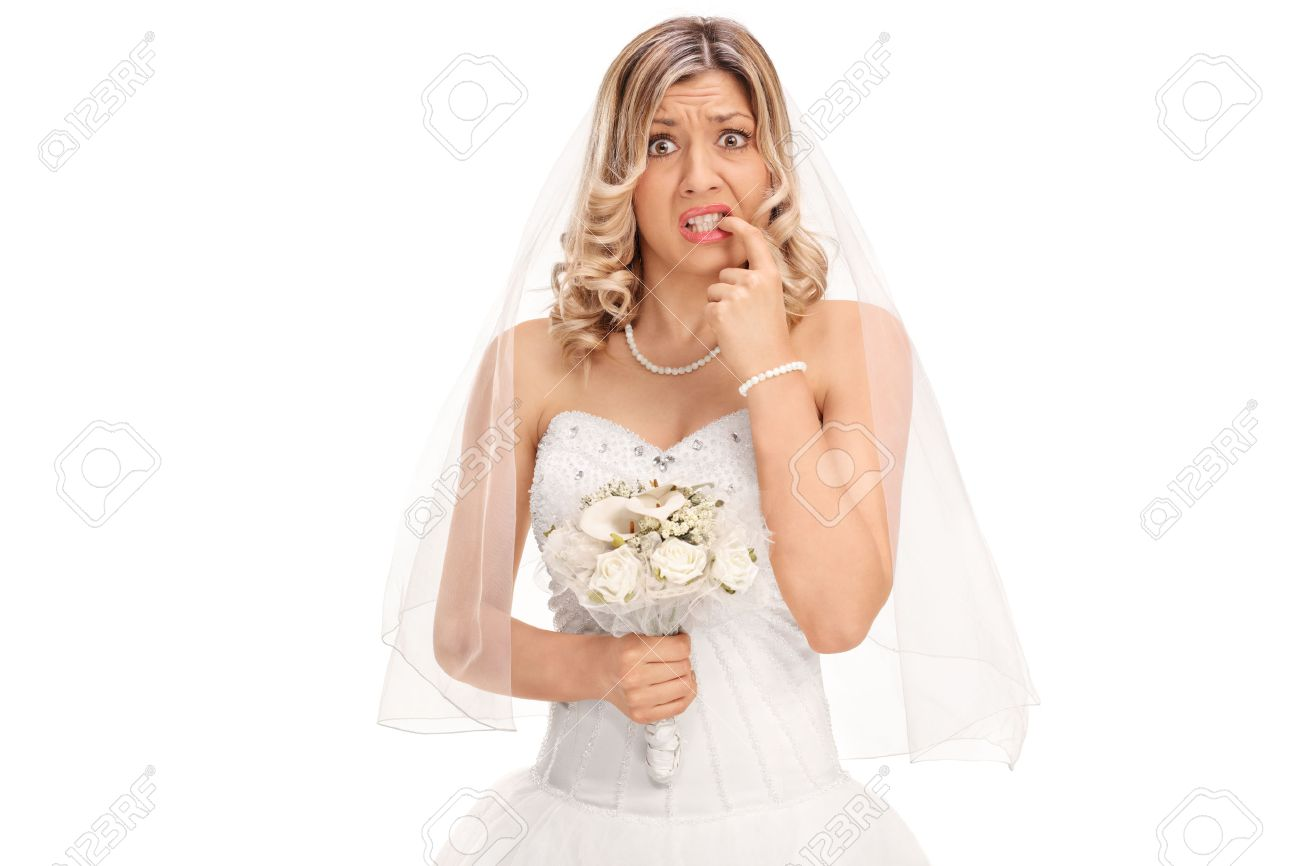 Nervous young bride biting her nails and looking at the camera isolated on white background - 54146674
