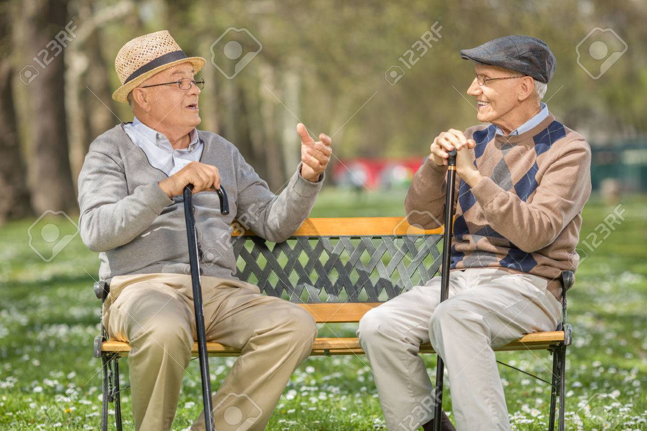 Two cheerful senior gentlemen talking to each other seated on a bench in a park - 55832108