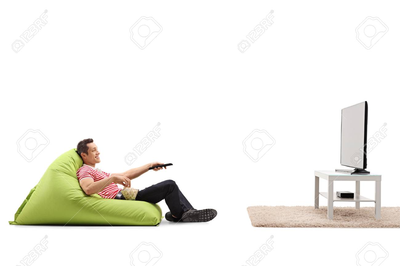 Relaxed man sitting on a comfortable green beanbag and watching TV isolated on white background - 59887673