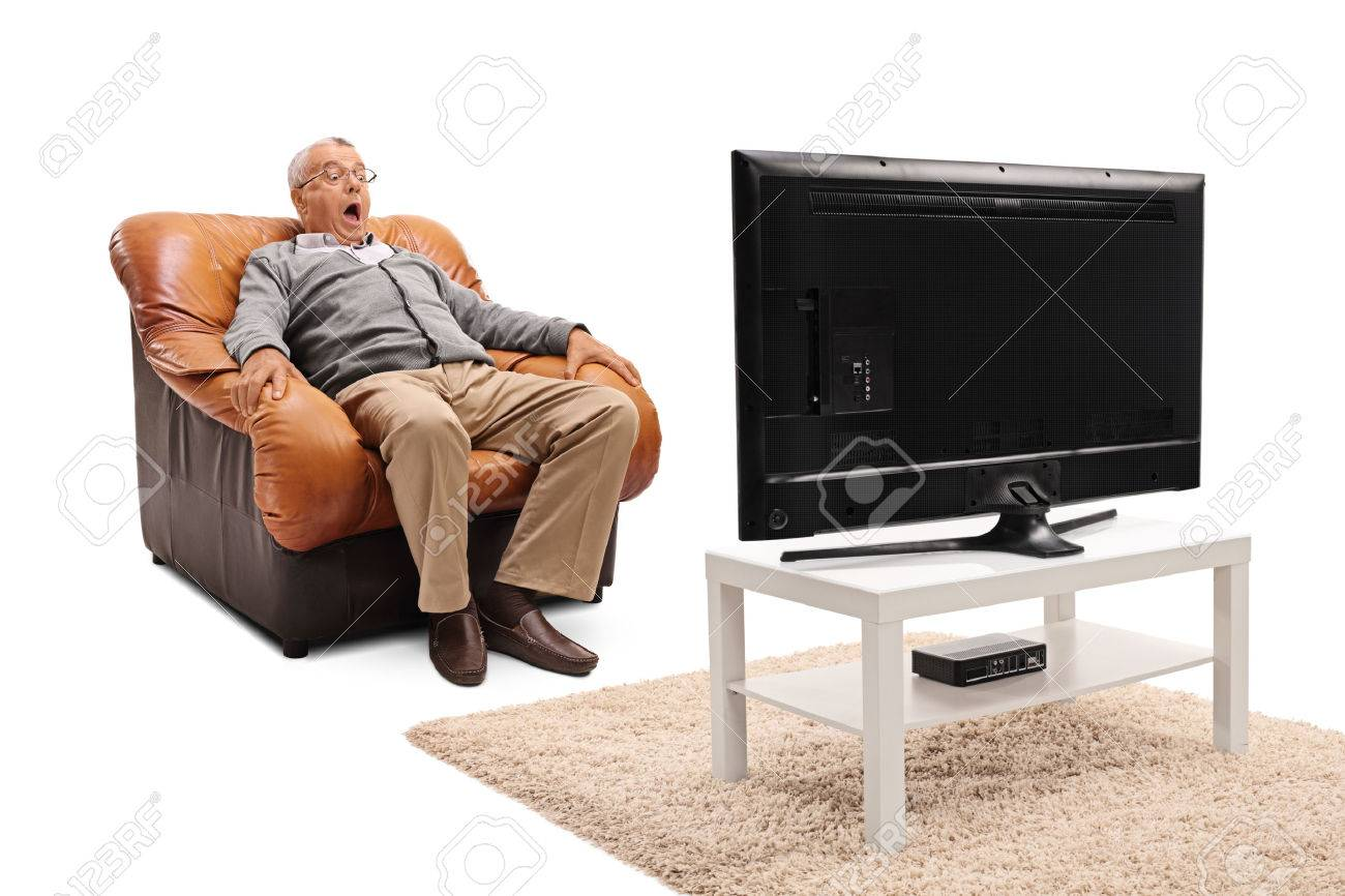 Terrified senior watching a scary movie on TV seated on an armchair isolated on white background - 60652075
