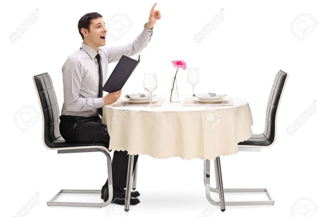 Young man calling the waiter and sitting at a restaurant table isolated on white background - 60812207