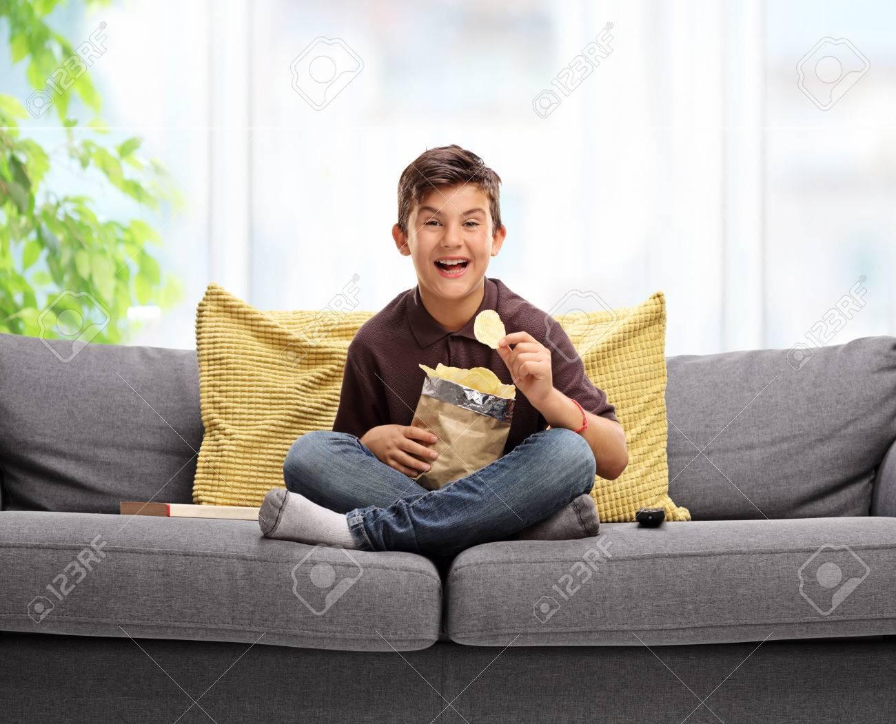 Joyful little boy sitting on a sofa and eating potato chips - 65941460