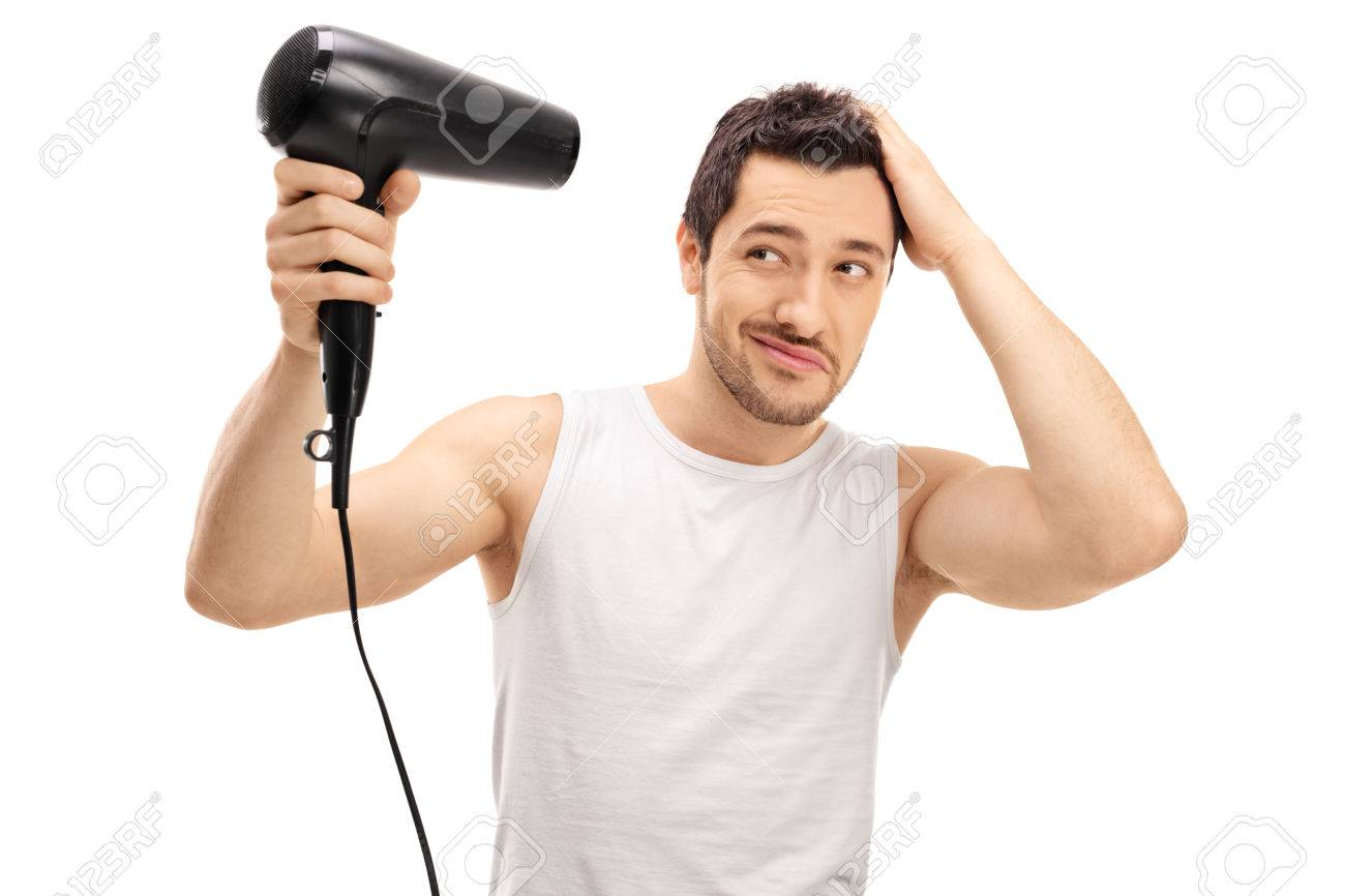 Handsome guy blow drying his hair isolated on white background - 69399696