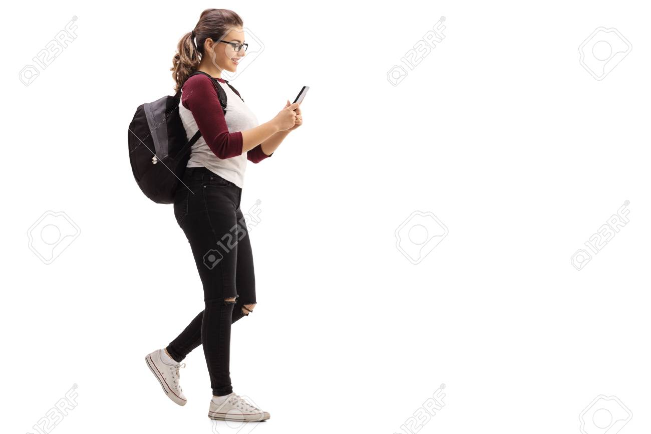 Full length profile shot of a female student walking and looking at a mobile phone isolated on white background - 70550083