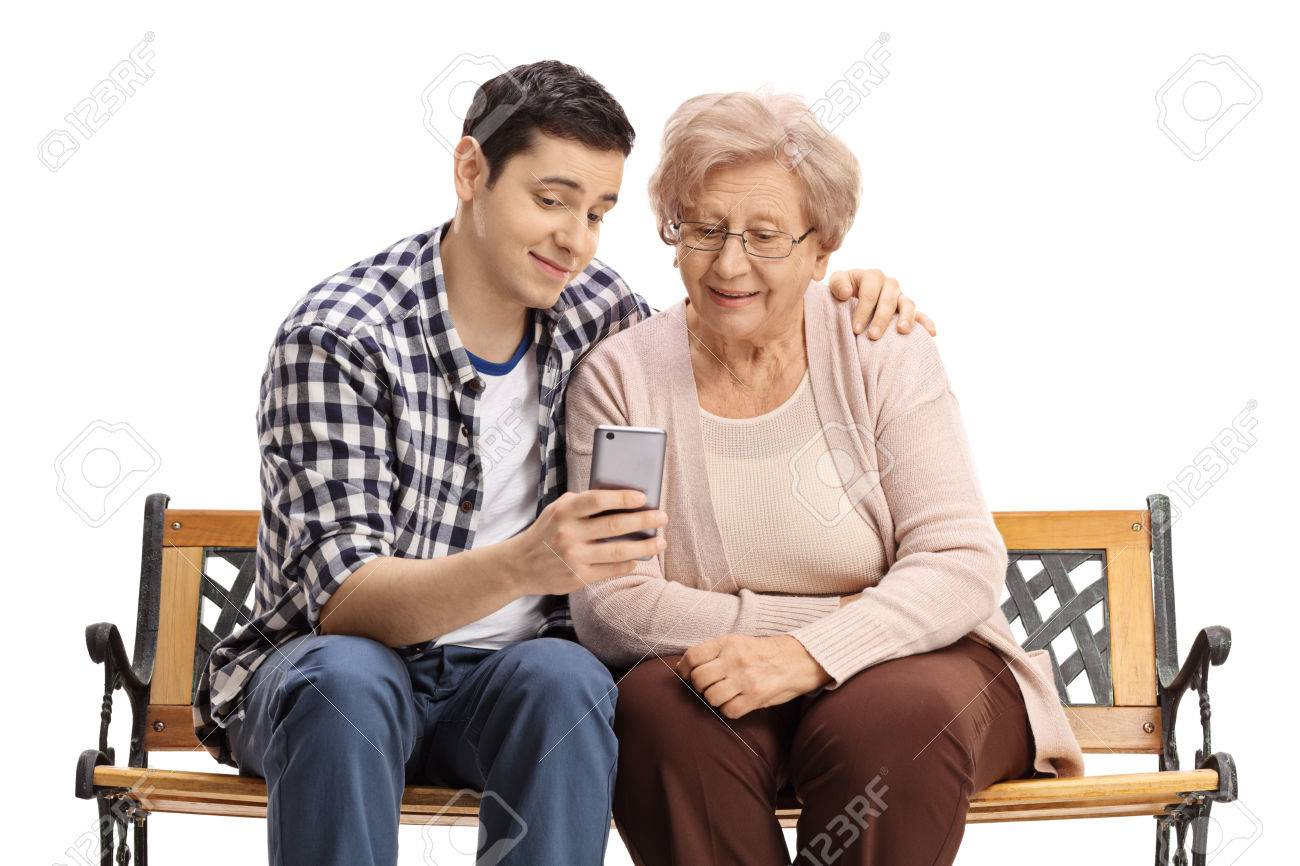 Young man sitting on a bench with a mature woman and showing her something on a phone isolated on white background - 72595169