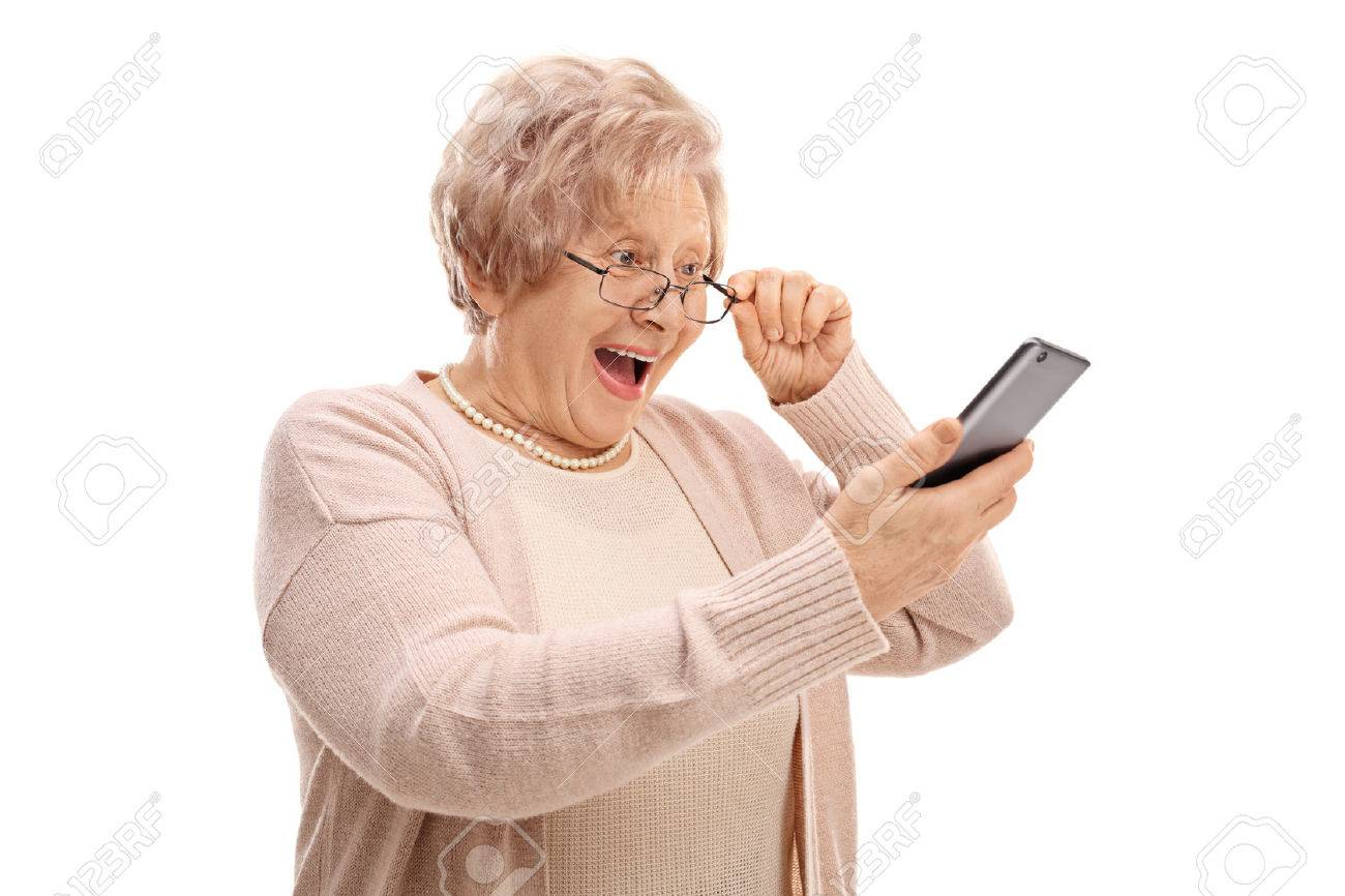 Excited senior looking at a phone isolated on white background - 72995987