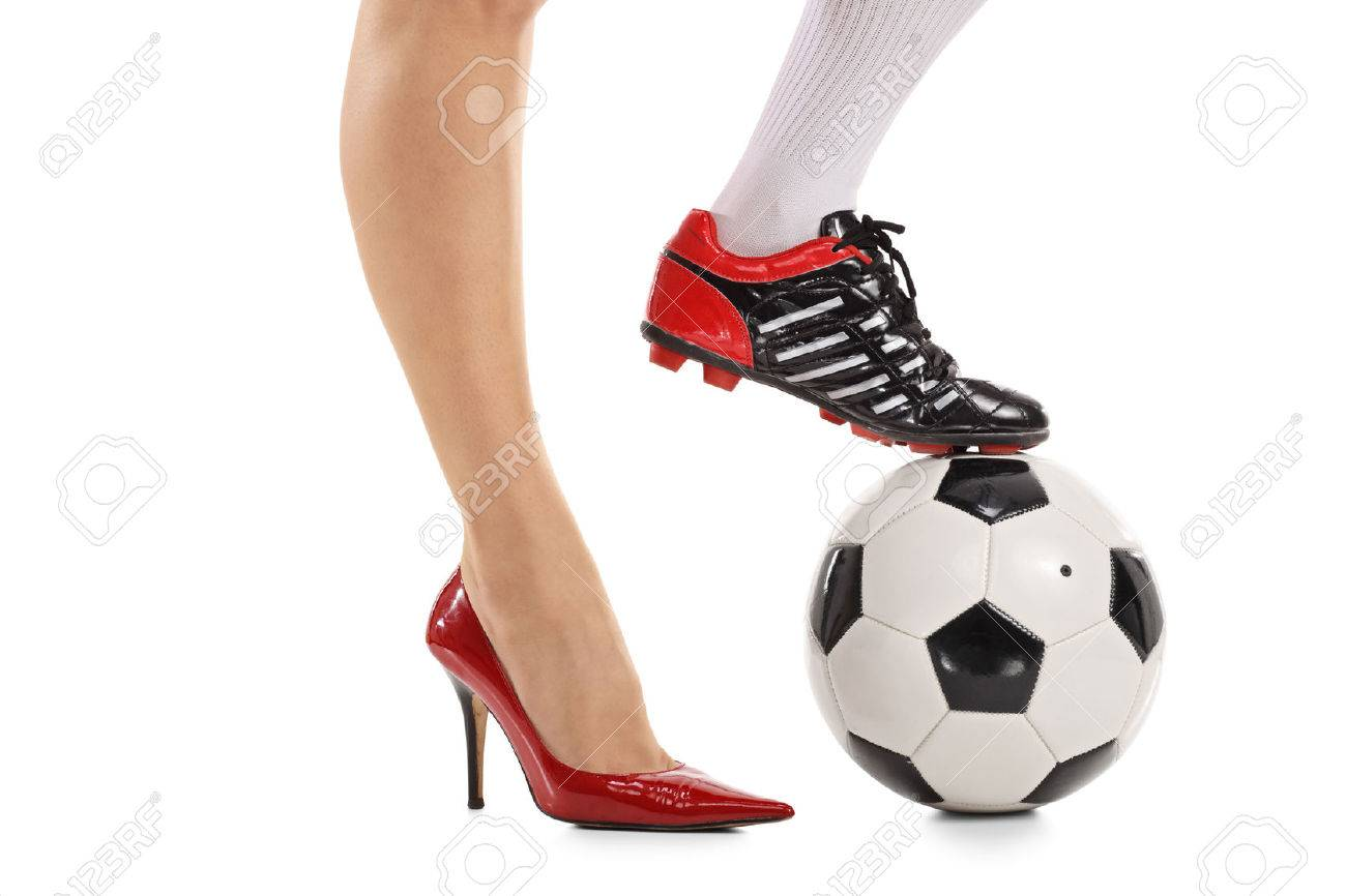 Woman with one foot in a high-heeled shoe and other in a soccer shoe pressing a football isolated on white background - 72996064