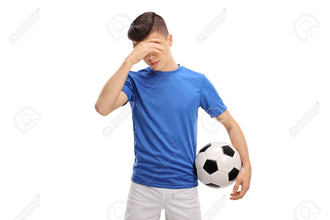 Upset teenage football player holding his head in disbelief isolated on white background - 75755742