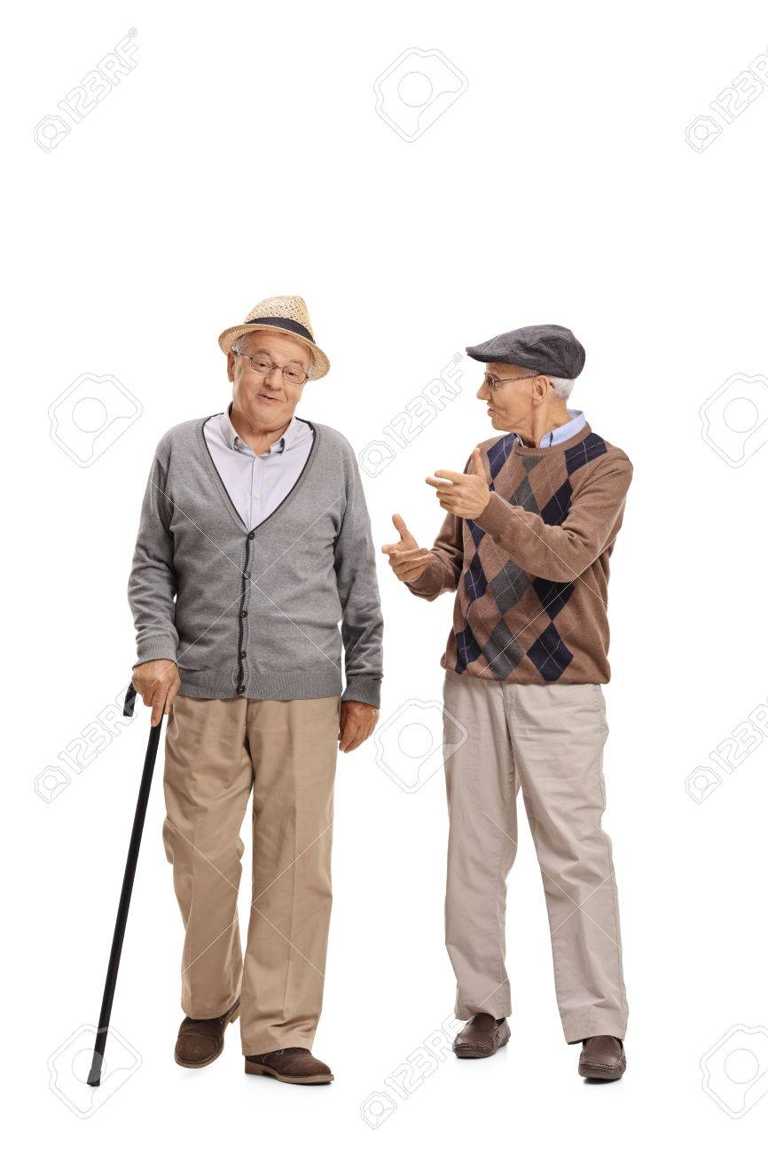 Full length portrait of two elderly men walking towards the camera and talking to each other isolated on white background - 76713473