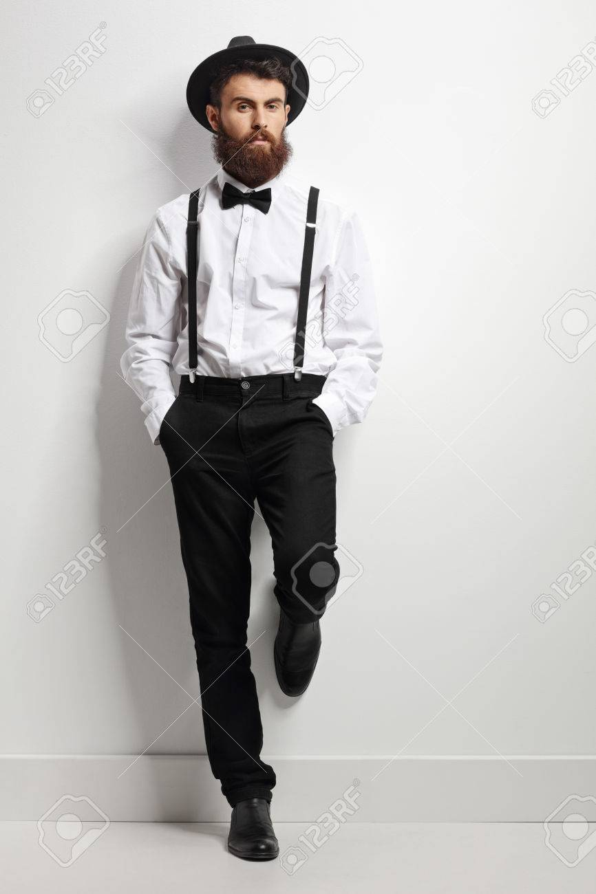 3f9f784461ab Full length portrait of an elegant man with suspenders and a bow tie  leaning against a