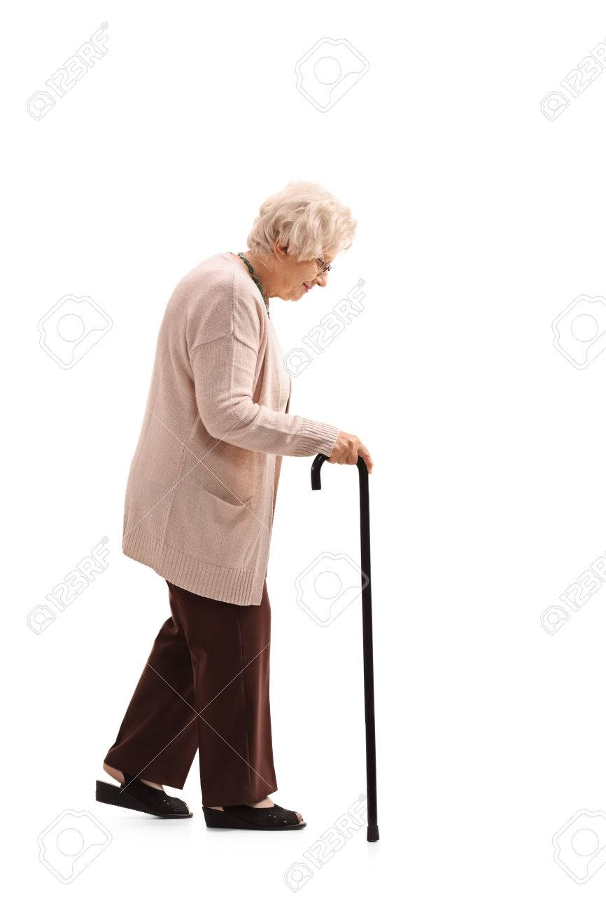 Full length profile shot of an elderly woman with a walking cane isolated on white background - 78649915