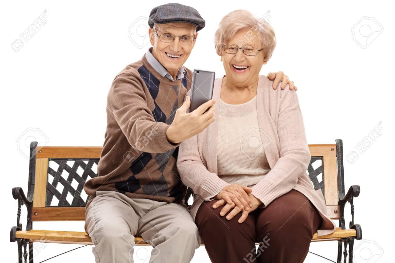 Op Een Bankje.Senioren Zitten Op Een Bankje En Nemen Een Selfie Geisoleerd Op