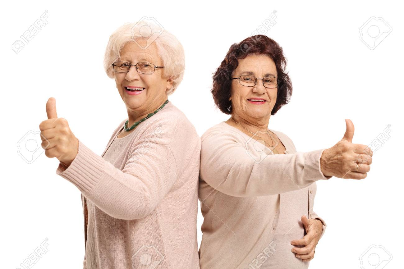 two cheerful mature women holding their thumbs up and looking