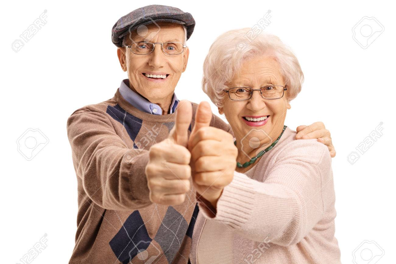 Cheerful mature couple making a thumbs up gesture isolated on white background - 80729854