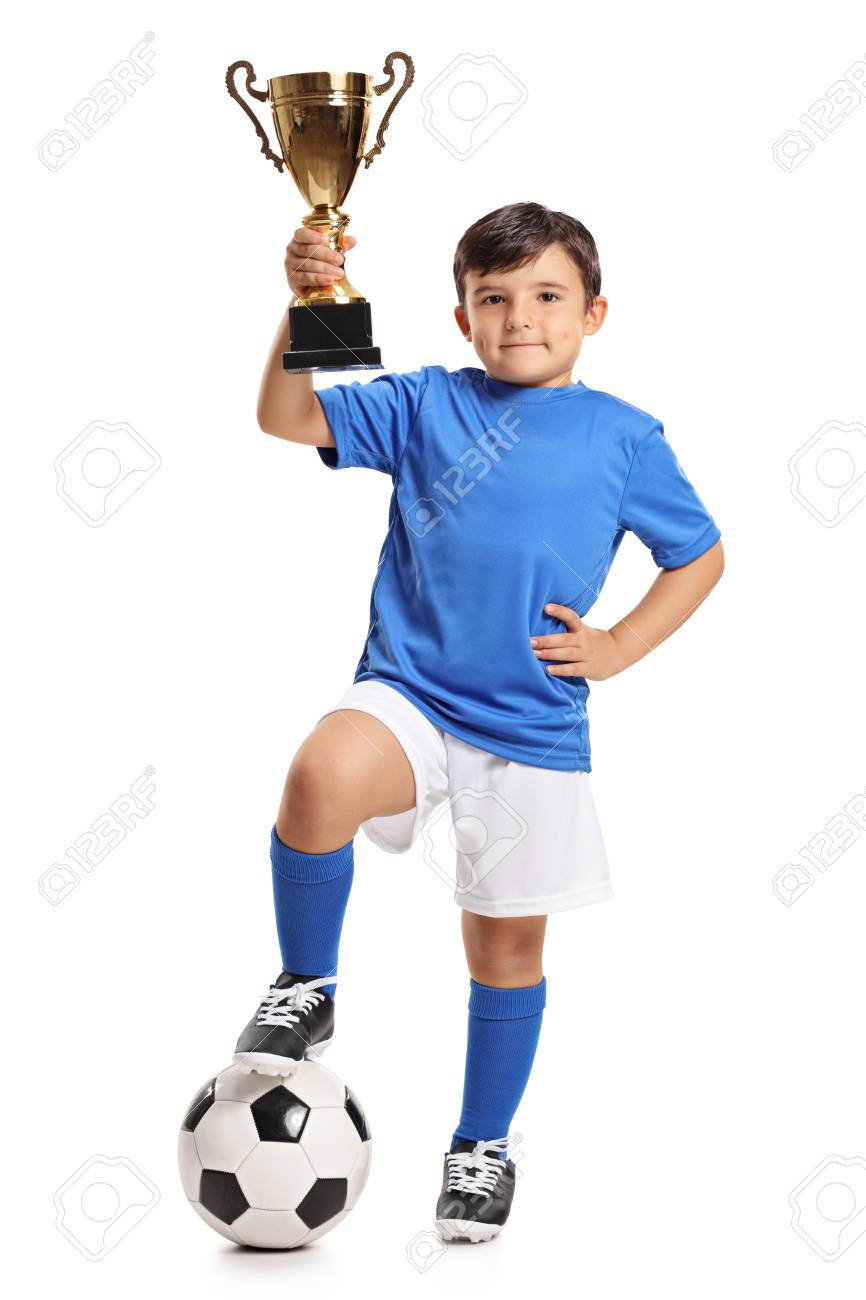 Full length portrait of a small boy in a blue jersey with a football and a gold trophy isolated on white background - 87592724