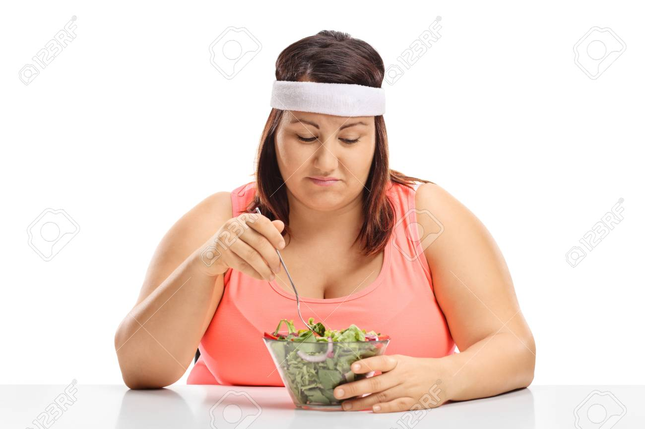 Sad overweight woman sitting at a table and looking at a bowl of salad isolated on white background - 89306213