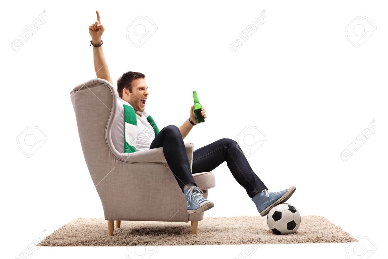 Excited football fan with a scarf and a beer bottle seated in an armchair pointing up with his finger isolated on white background - 90263737
