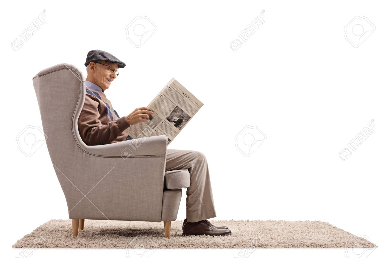 Senior seated in an armchair reading a newspaper isolated on white background - 91556227