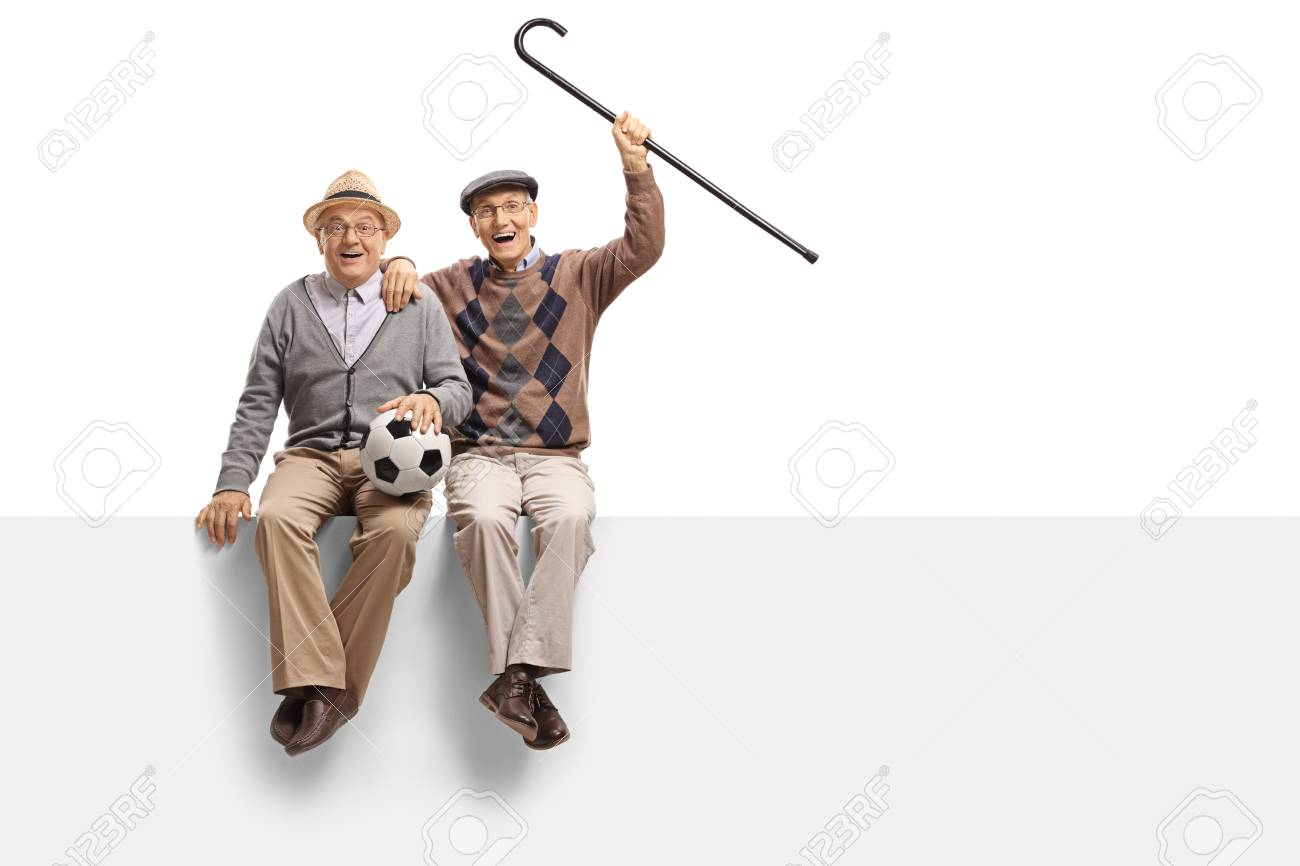 Cheerful seniors with a football seated on a panel isolated on white background - 92434893