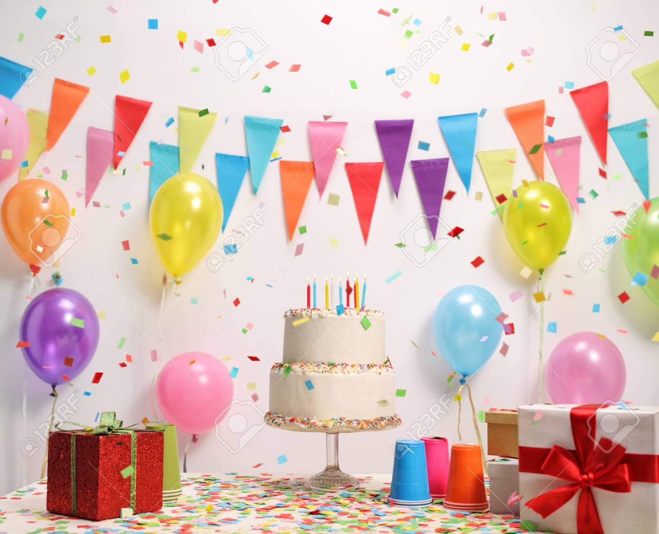 Birthday Cake On A Table Against Wall With Decoration Flags And Balloons Stock Photo
