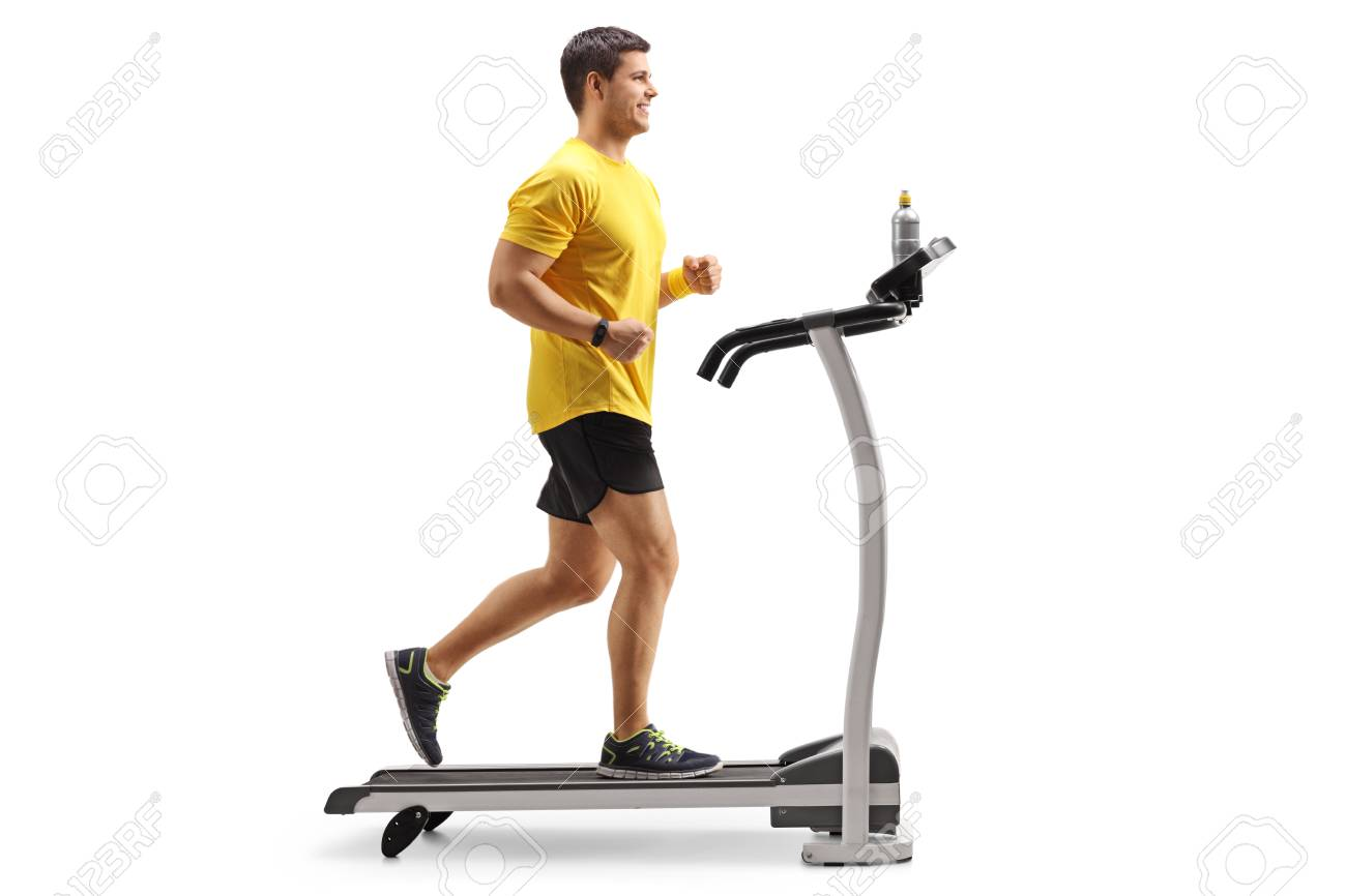 Full length profile shot of a young man running on a treadmill isolated on white background - 96528533