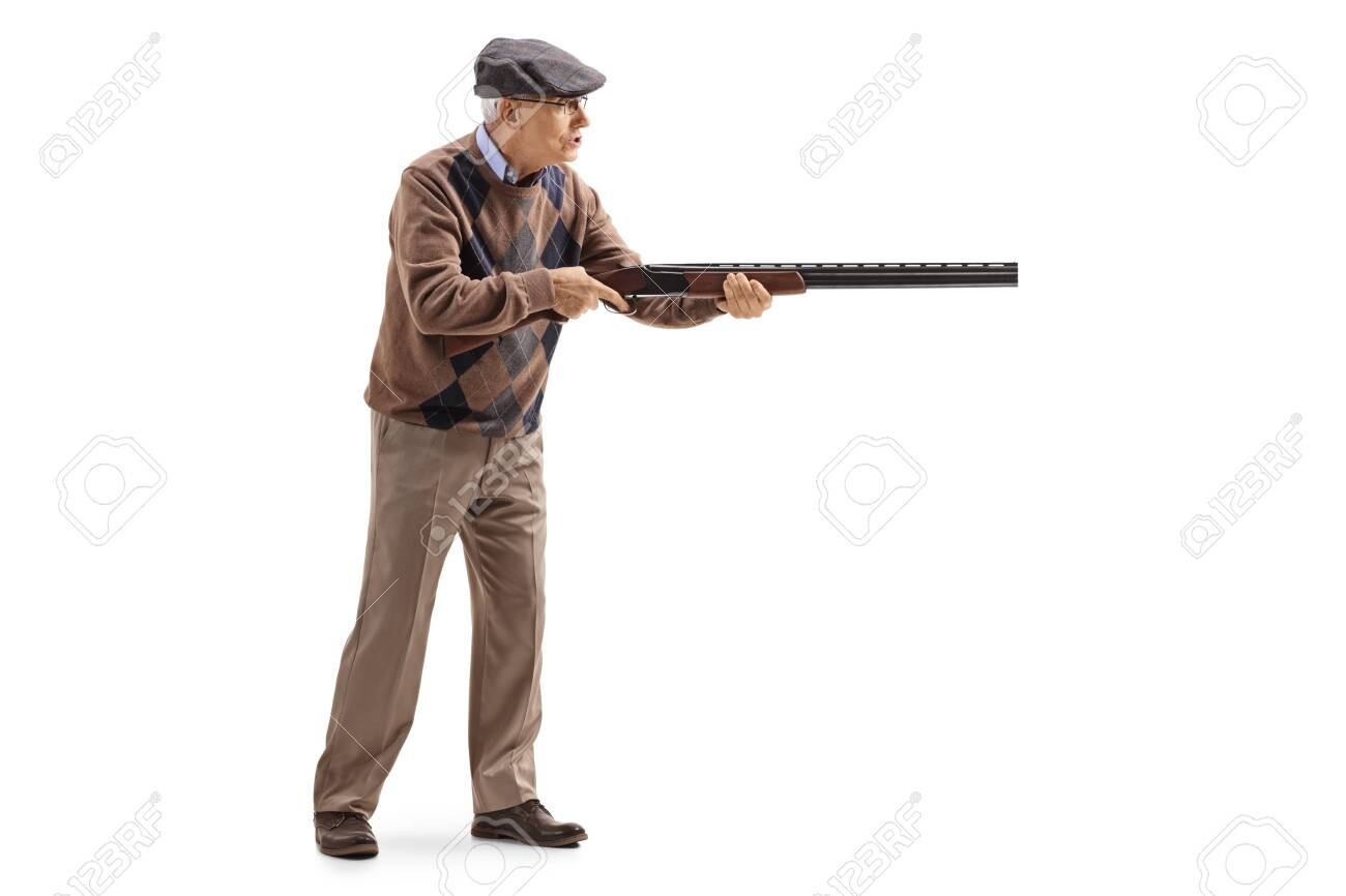 Full length profile shot of an elderly man aiming with a shotgun isolated on white - 122320735
