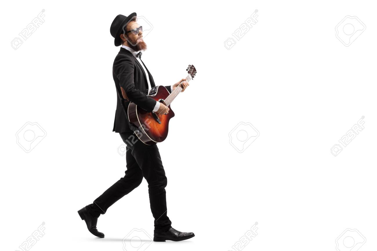 Full length profile shot of a male musician walking and playing an acoustic guitar isolated on white background - 124977195
