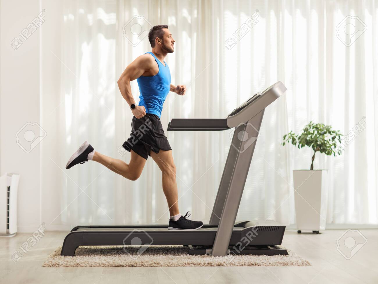 Full length profile shot of a young man running on a treadmill at home - 129384973