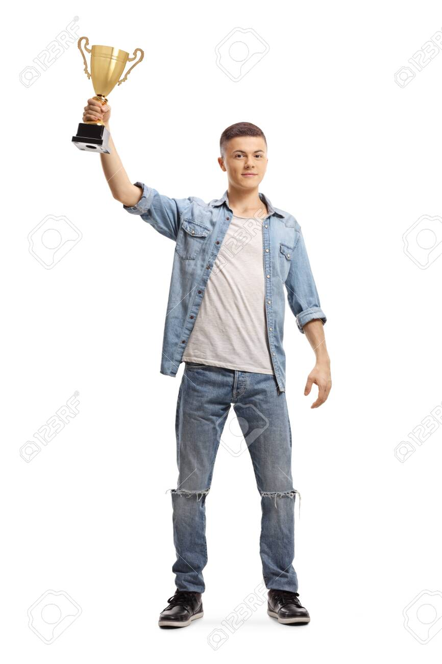 Full length portrait of a teenager holding a gold trophy cup up isolated on white - 129912259