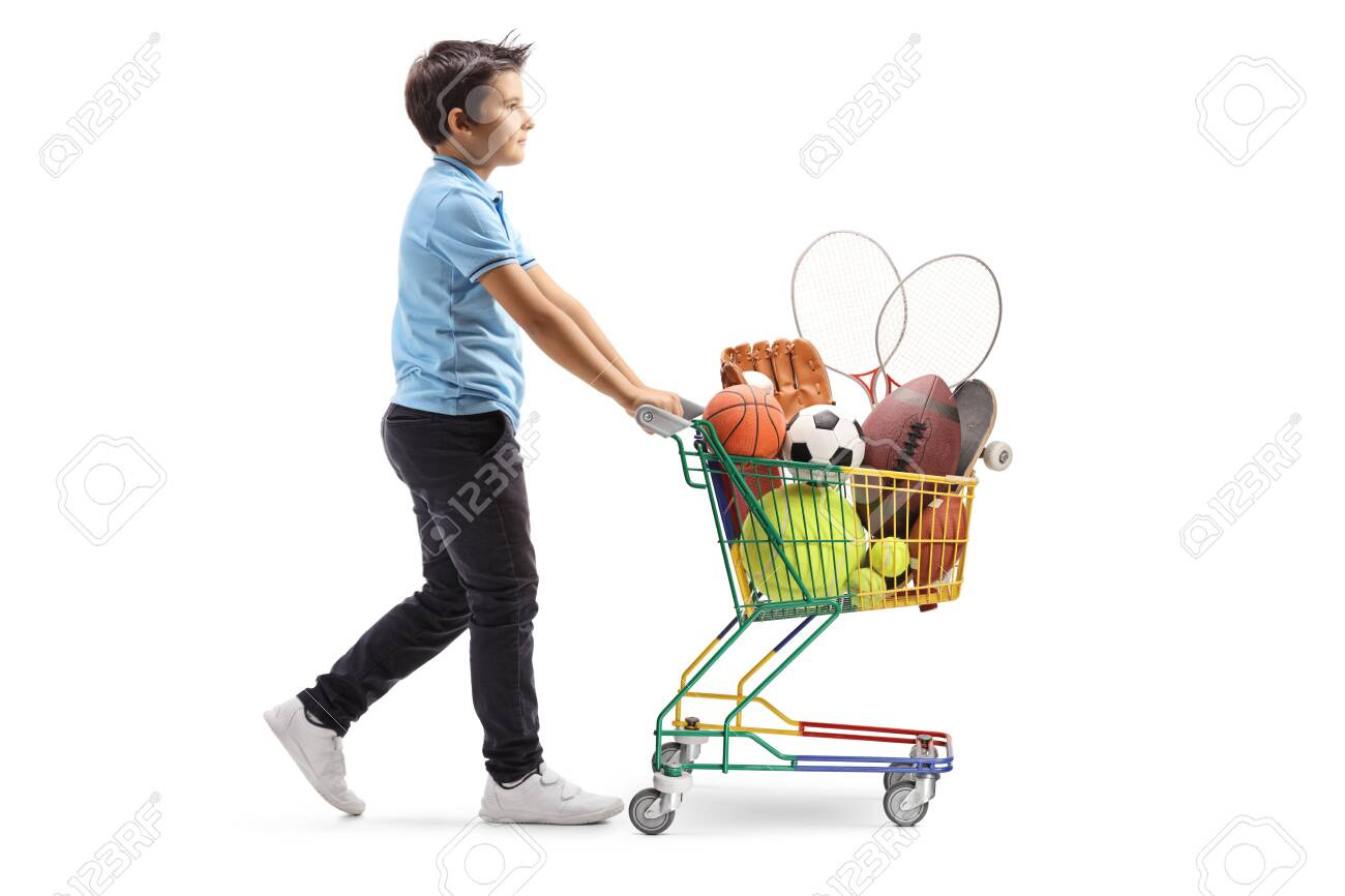 Full length profile shot of a boy walking and pushing a mini cart with sport items isolated on white background - 133106283