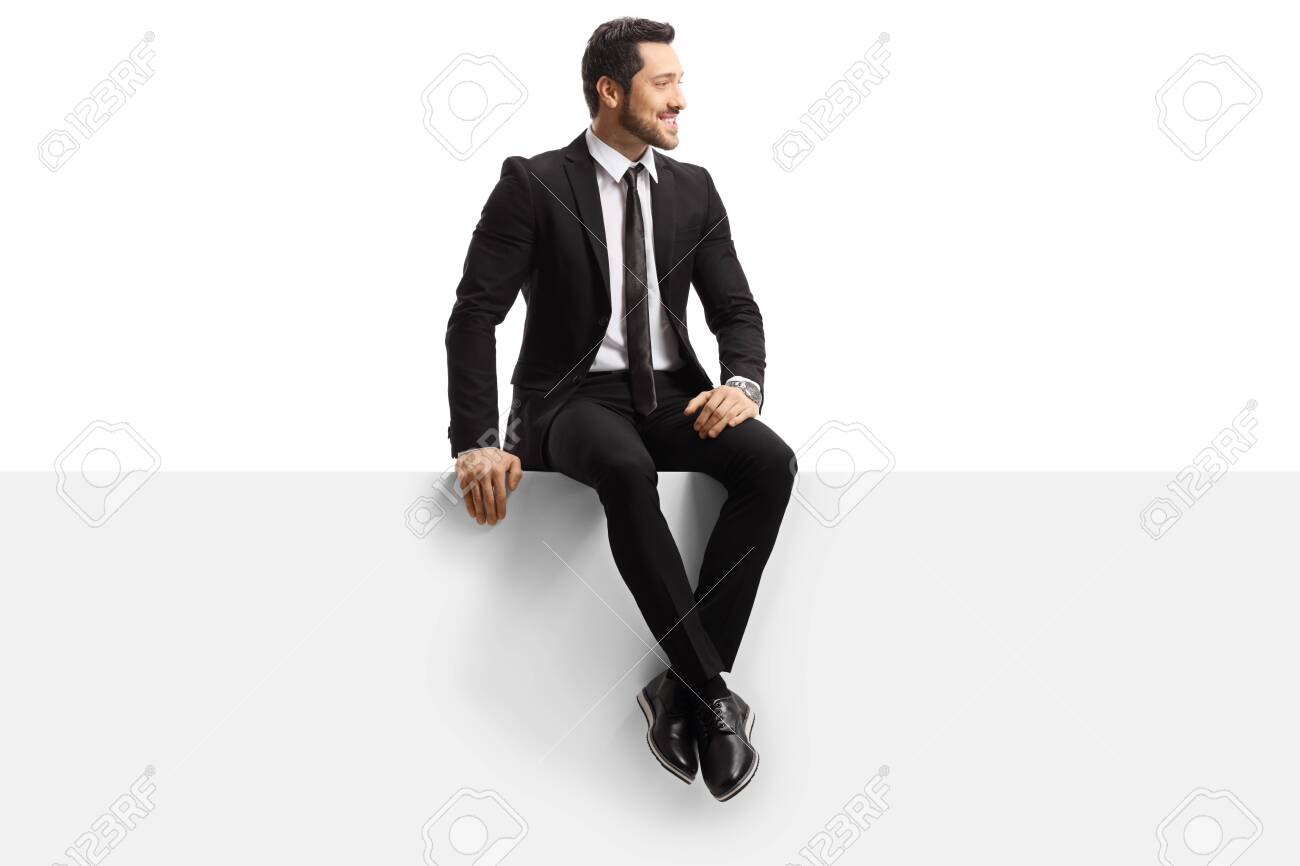 Young handsome man in a suit sitting on a panel isolated on white background - 134521565