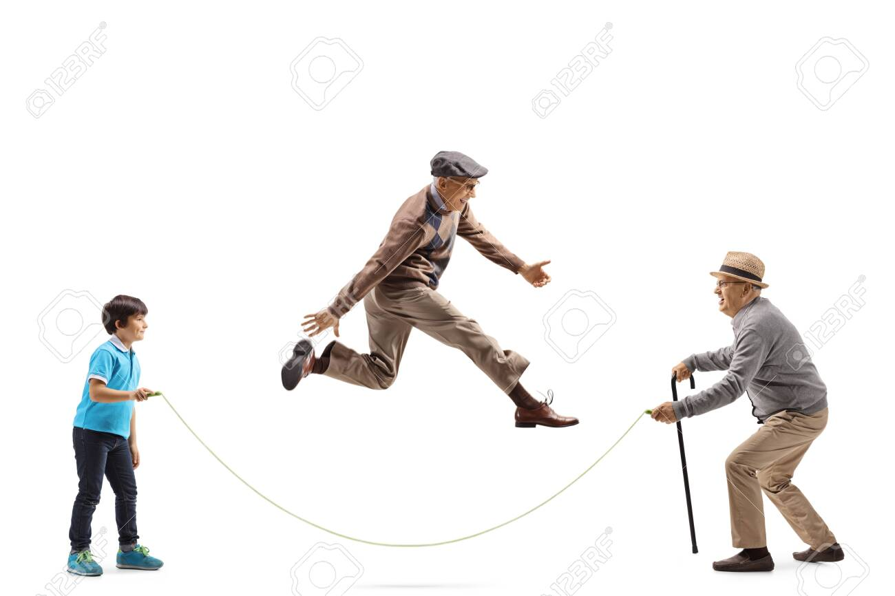 Full length profile shot of a grandfather and grandson holding a rope and an elderly man skipping isolated on white background - 138365954