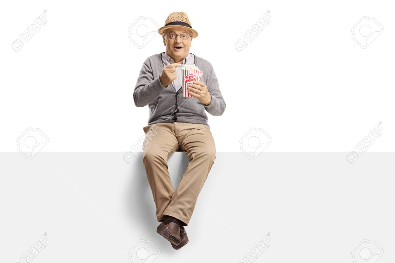 Excited mature gentleman sitting on a panel eating popcorn isolated on white background - 140553079