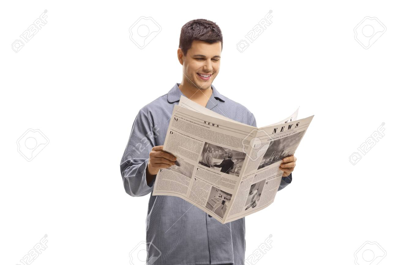 Man in pyjamas standing and reading a newspaper isolated on white background - 148997536