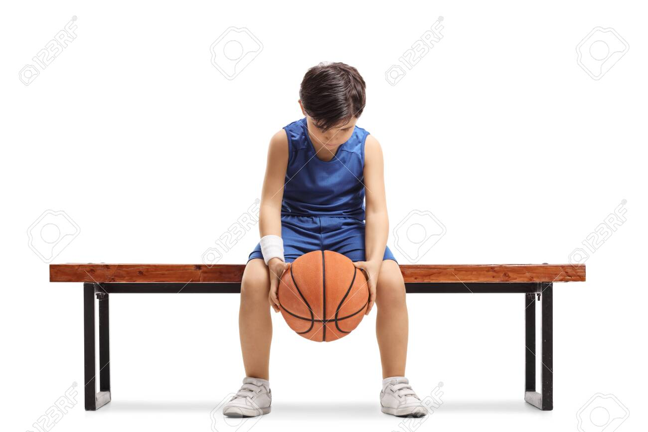 Sad little boy sitting on a bench with a basketball isoalted on white background - 151314744