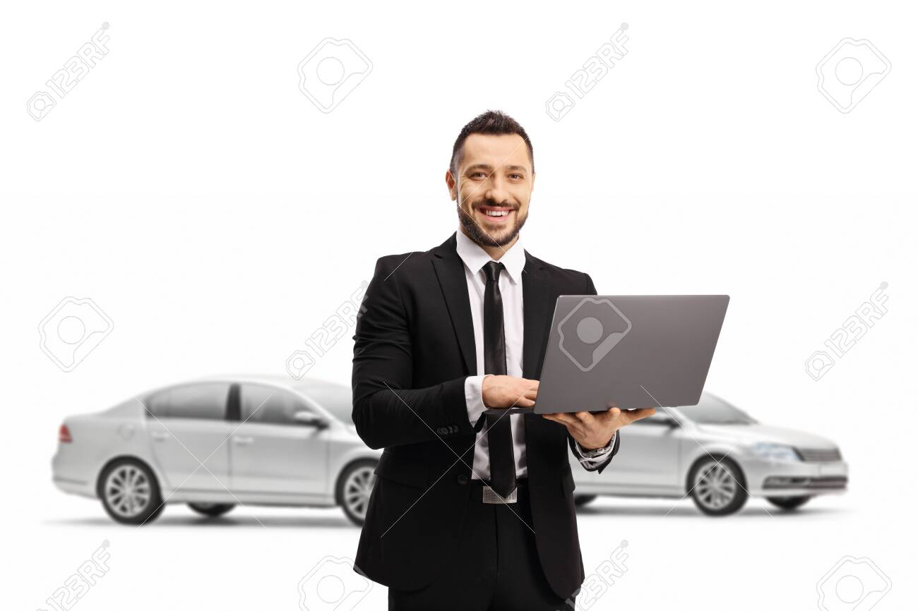 Man in a suit with a laptop computer smiling at the camera and posing in front of cars isolated on white background - 151314417