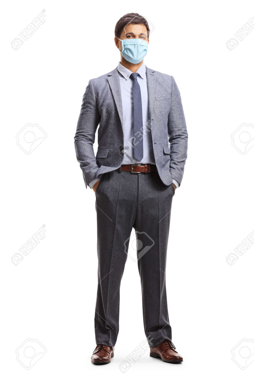 Full length portrait of a young man in corporate wear wearing a protective face mask isolated on white background - 153850530