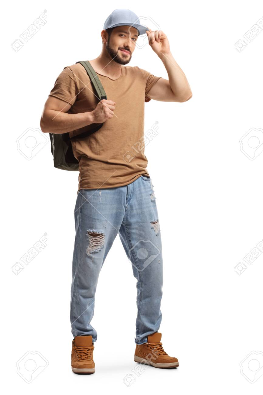 Full length portrait of a young man with a backpack and ripped jeans holding his cap isolated on white background - 156904995
